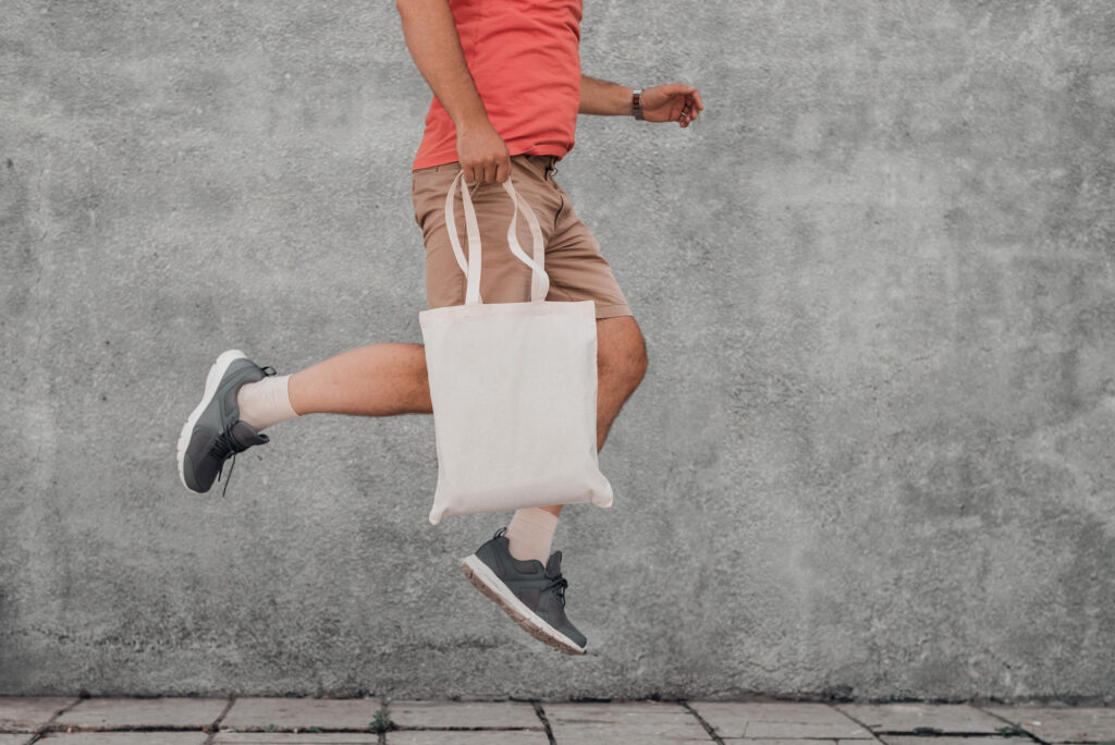 Young man is jumping with white cotton bag in his hands. Mock-up.