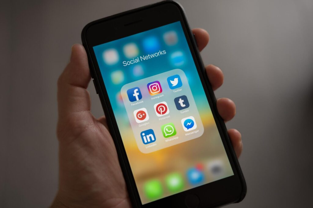 Social media platforms on phone in hand