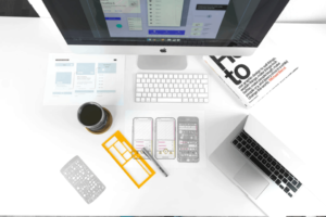 A desk with Mac computers, coffee, and design tools